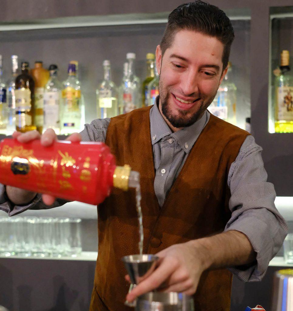 Bartender pours baijiu into jigger