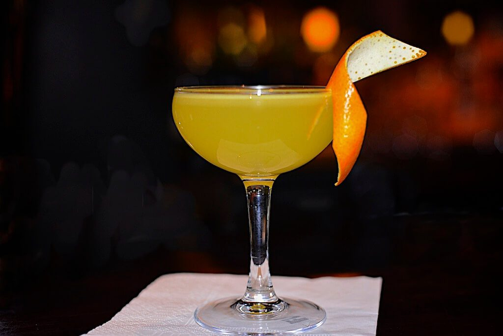 Yellow baijiu cocktail with orange peel