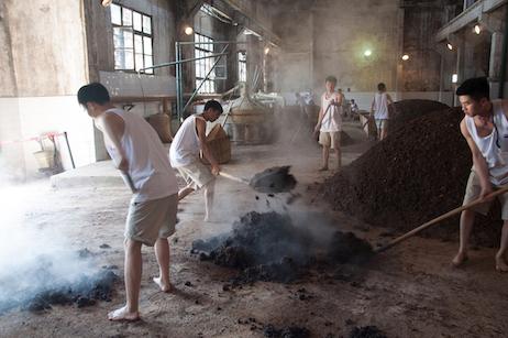 Baijiu workers shoveling mash